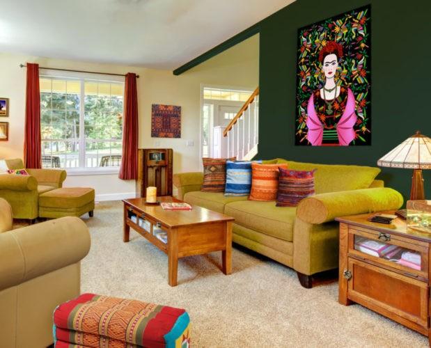 Parede amarelinho claro no fundo, na frente parede verde. Sala bem colorida, sofá amarelo e almofadas laranja