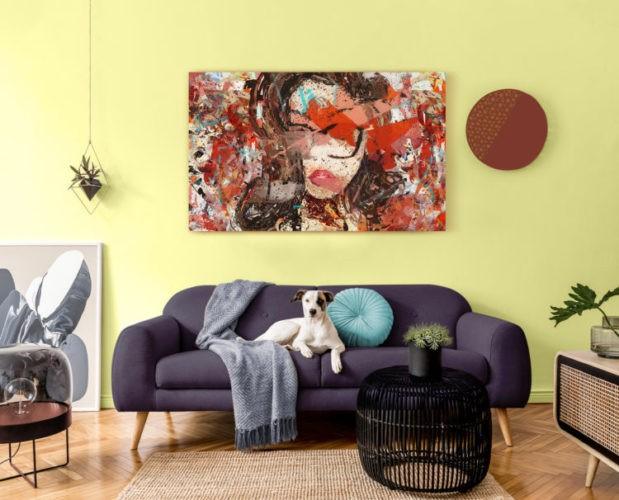 Parede pintada de amarelo claro, um tela abstrata vermelha penurada, na frente um sofá azul e um cachorro em cima