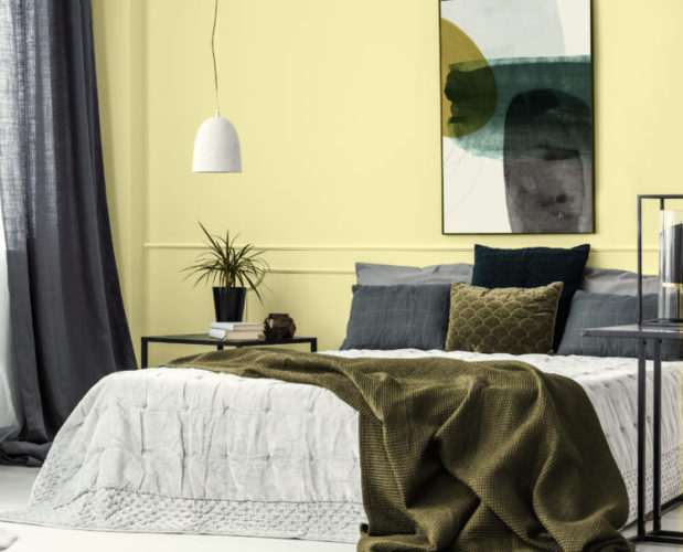 Manteiga de Cacau é eleita a Cor do Ano de 2021 pela Tintas Eucatex, um amarelo suave que nos remete a experiências de deleite e prazer. Pintada atras da cama em um quarto de casal. Cortinas e roupa de cama cinza completam o ambiente.