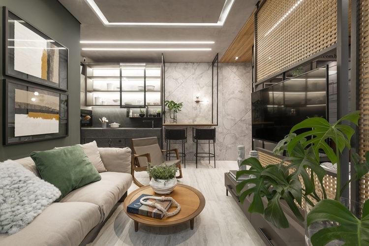 Mostra Janelas CasaCor. Sala multiuso com cozinha integrada. Parede verde, sofá cinza, em frente painel vazado de madeira com a tv