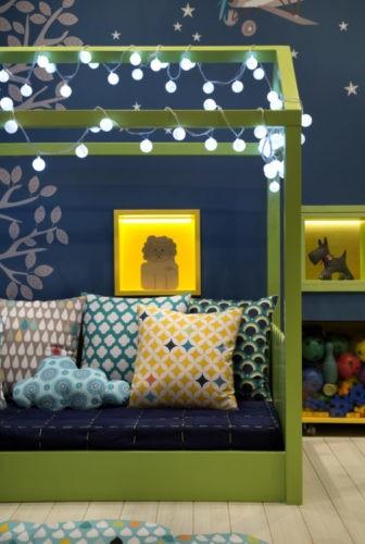 Quarto de criança bem colorido, cama baixa na cor verde em forma de casinha e fio de luzes em volta. Parede de fundo azil e nichos verdes iluminados