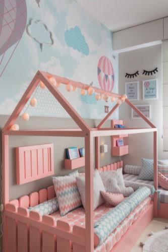 Cama baixa, no estilo Montessoriano. Cama na cor rosa, com desenho de casinha.