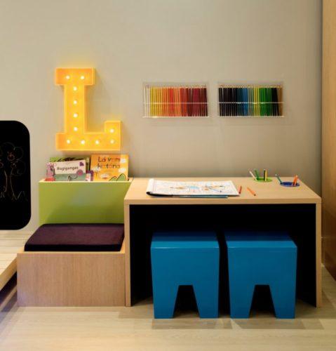 Cantinho em para desenhar em um quarto de criança. Bancada baixa, dois banquinhos azuis, na parede duas caixas de acrilico cheias de lápis coloridos e ao lado uma letra L com luz