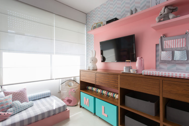 6 dicas que você precisa levar em conta na hora de montar o quarto do bebê. Móvel em medeira escura projetado sob medida, com gavetas, trocador e embaixo caixa para organizar brinquedos.