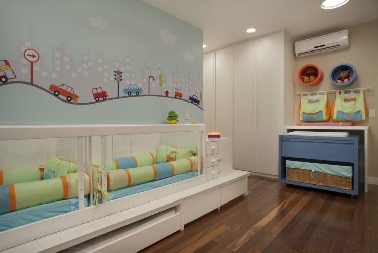 6 dicas que você precisa levar em conta na hora de montar o quarto do bebê. Dois berços ladoa lado em cima de um tatame. Papel de parede com carrinhos