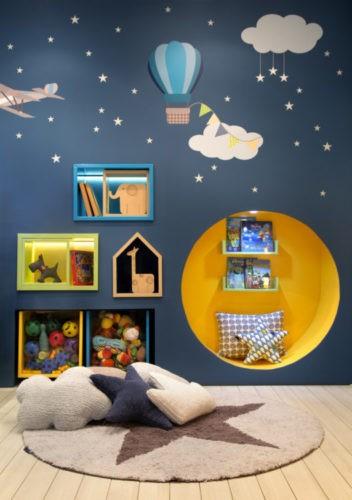 Quarto de bebê com papel de parede com motivos do ceú, com estrelas e nuvens. Um nicho amarelo grande embutido na parede.