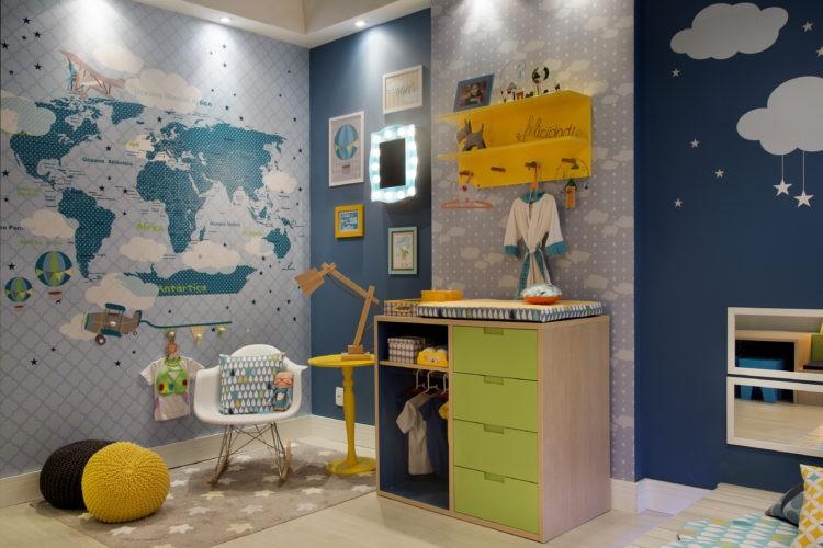 Quarto de criança bem colorido, papel de parede en ton s de azul com o mapa mundi, trocador em madeira com gavetas verdes.