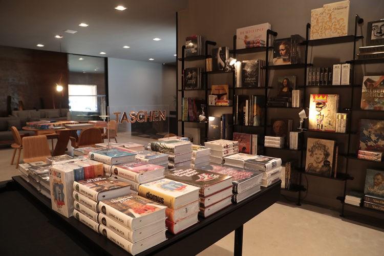 """Abertura da exposição """"Taschen 40"""", na loja da Mula Preta. Mesa quadrada repleta de livros da editora"""