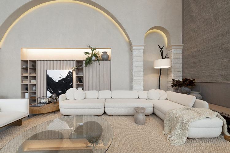 Ambientes abordam o novo morar no Janelas CASACOR /SC. Sala ampla e clara, comum grande sofá em L branco, e atrás arcos na parede