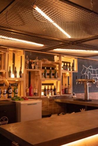 No bar da hamburgueria, caixotes de madeira com cervejas decoram o ambiente