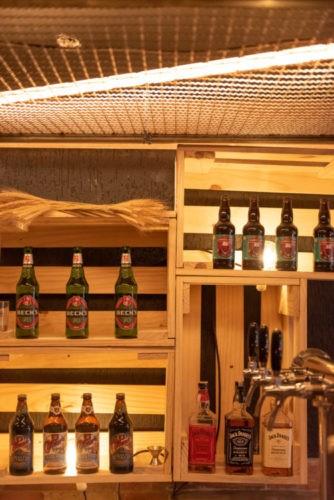 caixotes de madeira com garrfas de cerveja decoram o bar