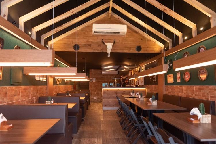 Hamburgueria decorada com madeira, no teto terças dão ideia de telhado e n fundo uma cabeça de boi na parede
