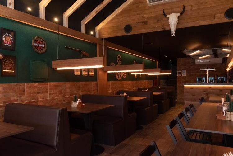 Hamburgueria decorada em clima Texano. Madeira no teto criando a ideia de telhado, uma cabeça de boi presa na parede
