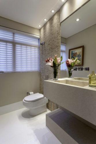 Lavabo decorado, parede com mosaicos em pedra e bancada em marmore