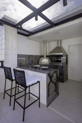 Cobertura em Salvador, canto da area externa com teto em vidro, churrasqueira e forno de pizza
