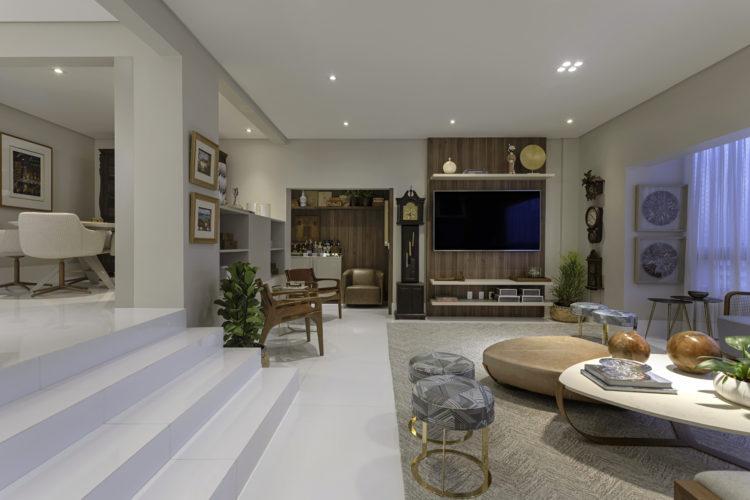 Ampla sala, desnivel de 4 degraus para cima leva a sala de jantar, piso em porcelanto branco, ao fundo painel em madeira para a tv e tapete bege