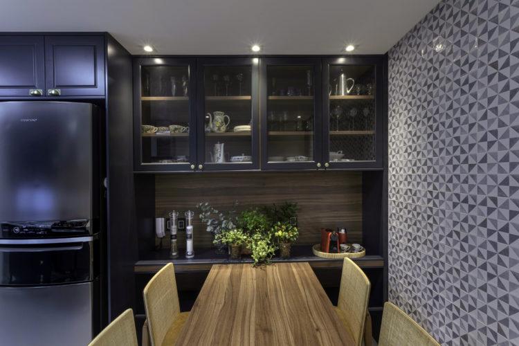 Cozinha decorada, parede revestida com azulejos decorados, armario em azul escuro com portas de vidro, embaixo uma bancada que sai uma mesa em madeira.