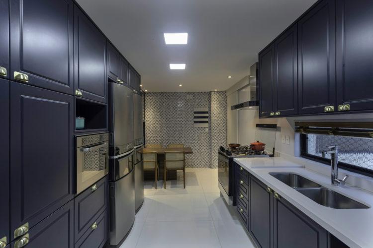 Cozinha em planta corredor, com armarios na cor azul marinho e bancada branca