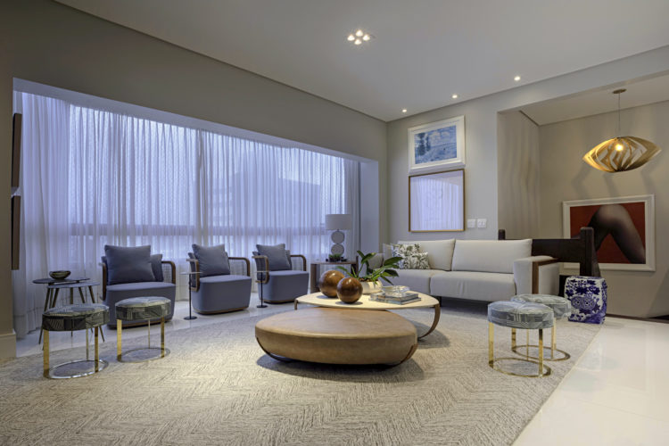 Projeto de cobertura em Salvador. Sala ampla e clara, com poltronas azuis e sofá branco.