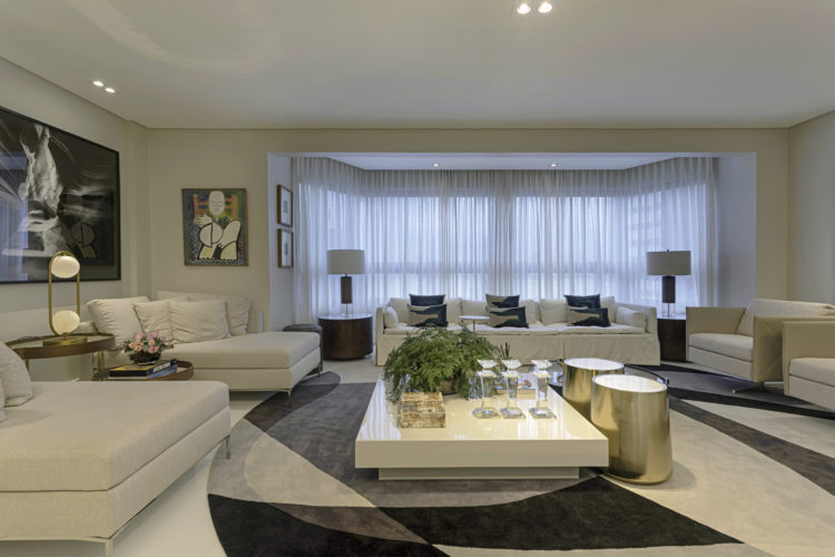 Projeto de cobertura em Salvador , sala ampla e clara. Sofá grande branco, duas chaises Loungues brancas ao lado , uma mesa de centro branca retangular e um tapete com desenhos geometricos azul, cinza e branco