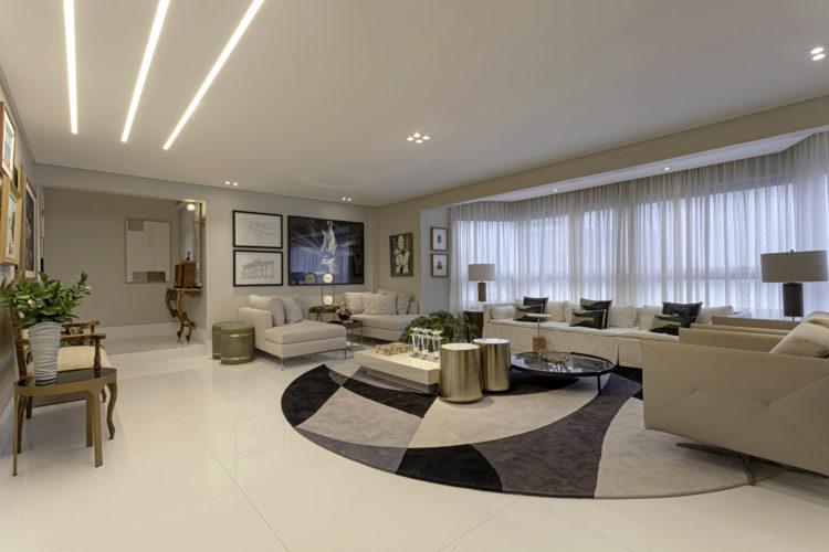 Sala grande e clara. Piso em porcelanato branco, sofá e poltrona brancos, um tapete na forma de circulo no centro, nas cores branco, azul e cinza
