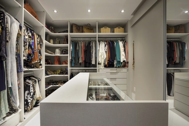 Closet feminino, com armarios em L e no meio um móvel .