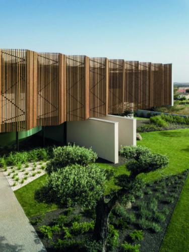 Ripas de madeira natural e colocadas na diagonal revestem a fachada da casa