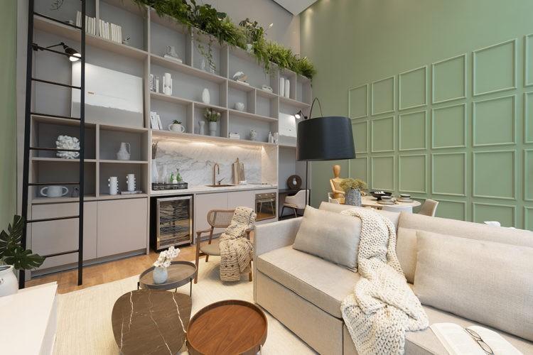 Espeço integrado, parede com estante de nicho e bancada de cozinha, com forno e mini geladeira embutida. Ao lado uma parede pintada de verde com molduras tipo boiserie da mesma cor.