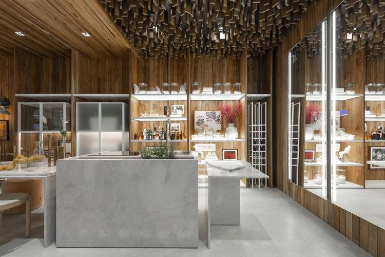 Cozinha toda revestida em madeira, teto e paredes e em determinado pedaço, pedaços de madeira pendurados criam um escultura