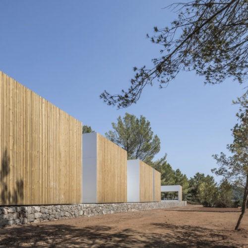 Solução em madeira natural para áreas externas sem aditivos reveste a fachada da casa de campo com arquitetura em blocos