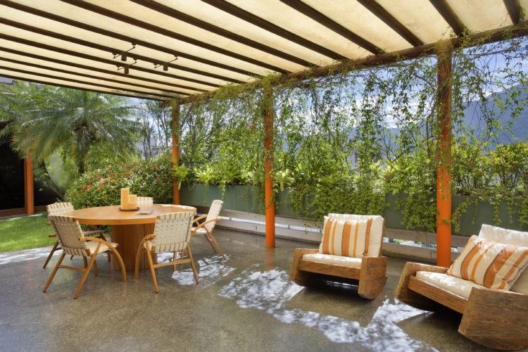 Terraço com pergolado em madeira, piso em granito, caeiras de design e uma mesa redonda. Ao fundo floreiras