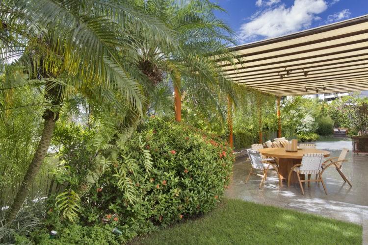Terraço em uma cobertura linear com cara de jardim de casa. Pergolado em madeira, ao lado pequeno gramado com coqueiros