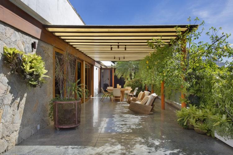 Terraço em uma cobertura linear com cara de jardim de casa. Parte coberta com pergolado em madeira, piso em granito e floreiras em frente a porta da sala