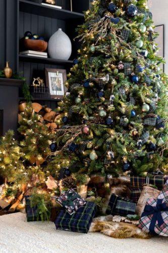Arvore de Natal grande com bolas azuis e presentes no piso