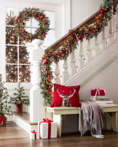 Prontos para decorar casa para o Natal?. Corrimão da escada enfeitado com cordão verde e bolas vermelhas.
