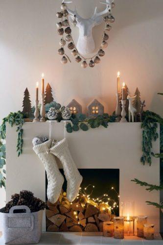 Decoração de Natal, lareira branca, botinhas brancs penduradas , velas e luzes em cima. Estilo escandinavo