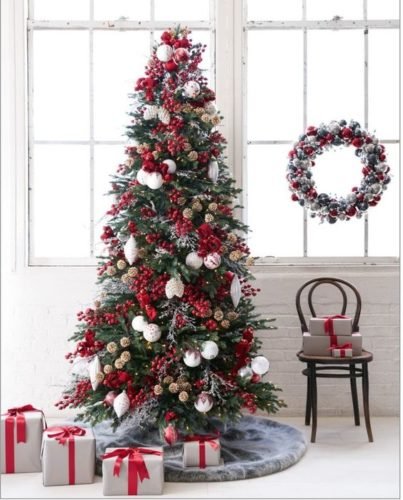 Paredes com tijolinho branco, contraste com a arvore de Natal com bolas vermelhas e no piso pacotes de presentes