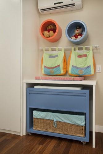 6 dicas que você precisa levar em conta na hora de montar o quarto do bebê. Trocador com móvel zul embaixo para guardar itens do bebê. Um varão com dois porta fraldas e emcima dois nichos redondos enfeitando.