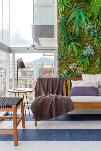 varanda com fechamento em cortina de vidro, parede verde e sofa em frente