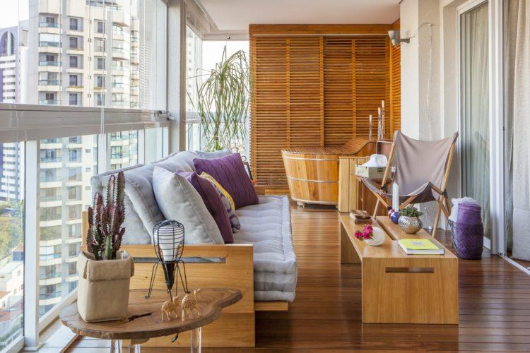 Varanda fechada com cortina de vidro, piso em madeira, sofá de futon e um ofuro no canto