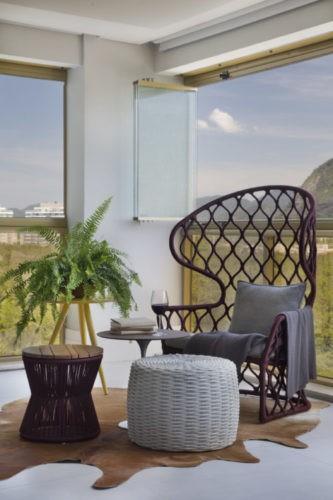 Varanda com fechamento em cortina de vidro, uma cadeira estilo Pavão e dois puffs em frente.