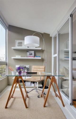 Varanda fechada com cortina de vidro e transformada em um home office. Mesa de vidro com cavalte de madera, luminaria de piso, e prateleiras na arede de fundo