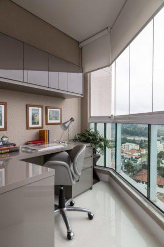 Varanda fechada com cortina de vidro, e transformada em um escritoro. Com bancada, gaveito e armario superior