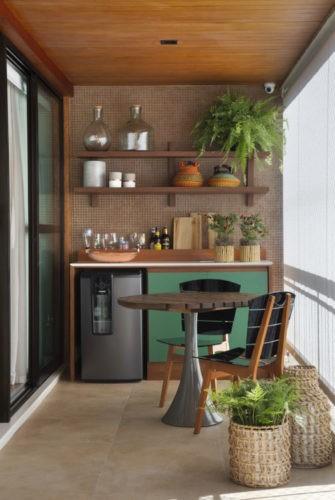 Cantinho da varanda com uma bancada, geladeira embaixo, armarios verdes ao lado. Na parte de cima, prateleiras com plantas e na frente uma mesinha redonda com duas cadeiras.