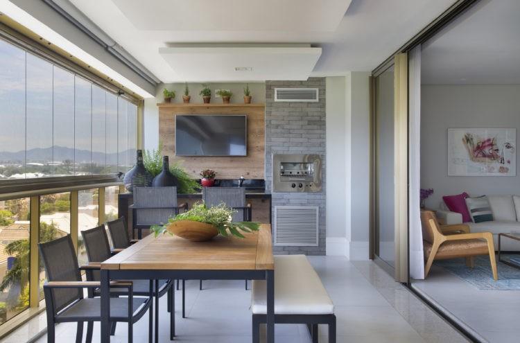 Varanda Gourmet, com churrasqueira, bancada , tv e uma mesa de madeira com cadeiras.