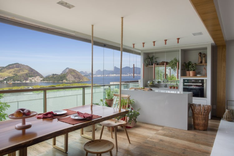 Varandas: dicas para decorar o ambiente. Espaço amplo, com uma ilha para cooktop, na parede de fundo um forno embitido e cuba. Ao longo da varanda uma mesa suspensa por cabos no teto
