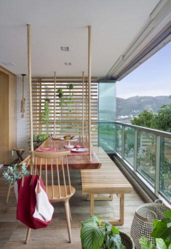 Varanda aberta, com uma mesa suspensa por cordas no teto , um banco de madeira e no fundo painel em madeira ripado