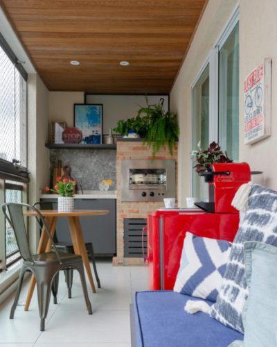 Varanda multiuso, churrasqueira ao fundo, teto revestido em madeira, mesinha redonda e sofá ao lado da mini geladeira vermelha