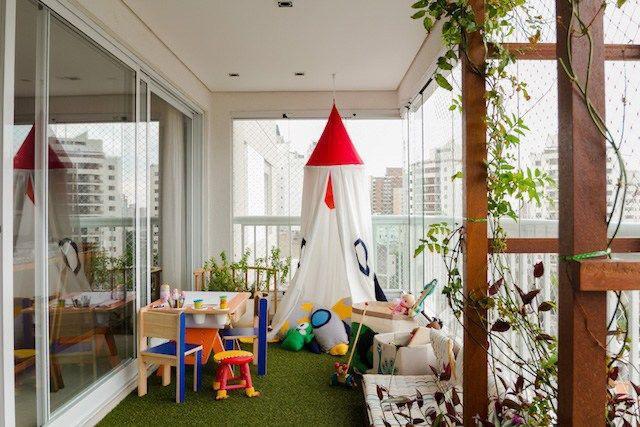 varanda fechada em cortina de vidro, grama sintetica no piso. Espaço transformado em um brinquedoteca.