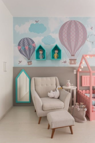 Papel de parede do quarto de beb~e com balões e na frente uma oltroba bege com puff